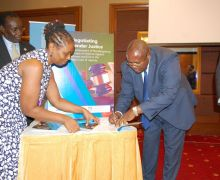Deputy chief justice hon justice Yorokamu Bamwine signs on a report on negotiating gender justice,as  executive director center for Domestic Violence Prevention Tina Musuya looks on,during the high level forum for judges on justice for women and girls 2018,at Sheraton hotel in Kampala on Thursday 29/2018.Photo by Sylvia Katushabe.
